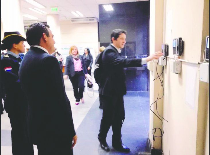Momento en que Petta observa cómo sus funcionarios marcan la entrada para el inicio de la jornada laboral.