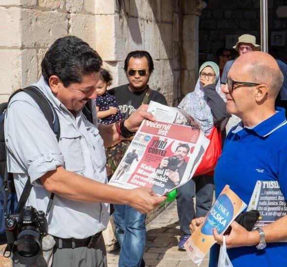 Yuri Cortez mira la tapa de un periódico croata donde aparece su foto. Fue recibido como un héroe.