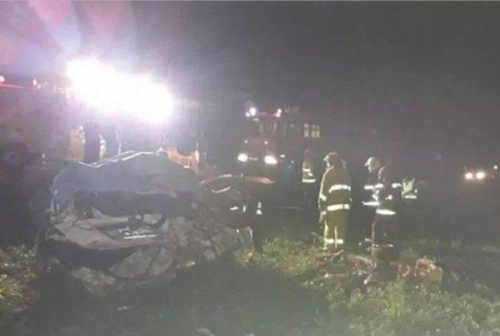 Momento en que bomberos voluntarios proceden a rescatar los cuerpos del interior del rodado.