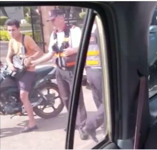 Momento en que el PMT recibe el dinero del motociclista.