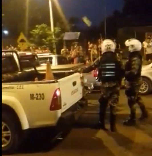 Momento exacto en que llega el globito de agua para impactar contra la cabeza de una agente del Grupo Lince (Captura de video: Info Alto Paraná).