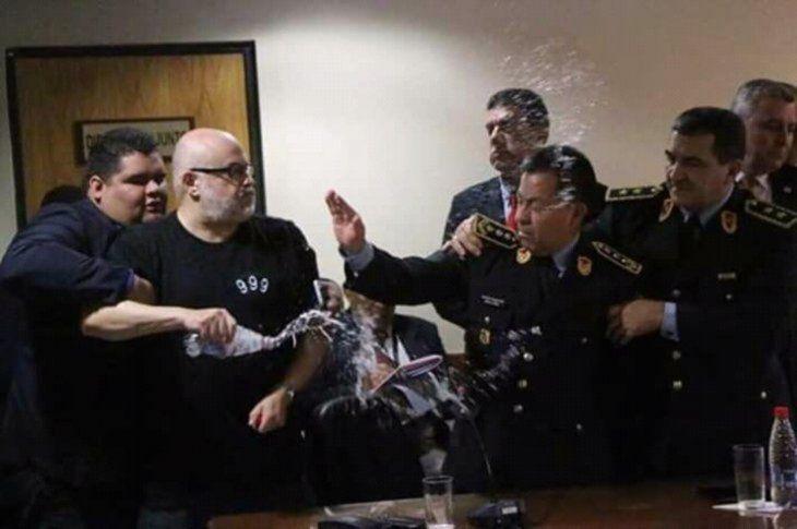 Momento en que Payo derramó agua alcomandante de la Policía Walter Vázquez.