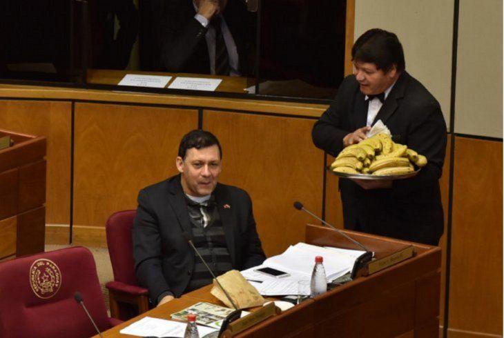 En una foto de archivo se ve a uno de los funcionarios repartiendo bananas a Víctor Bogado.