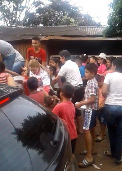 Niños agolpados para recibir una ración de comida