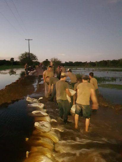 Militares intentando detener el agua con bolsas.