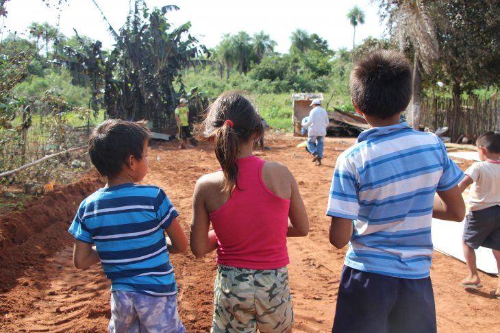 Los hermanitos mirando los restos de su casa.