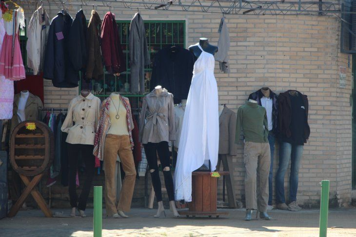 De blanco. El impecable traje de novia de corte imperio se destaca en el mercado de pulgas. A su alrededor otras prendas de segunda mano.